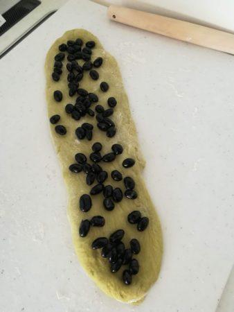 伸ばした生地に黒豆を乗せる